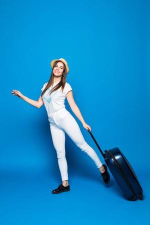 青い背景にスーツケースで走るファッショナブルな女性 写真素材