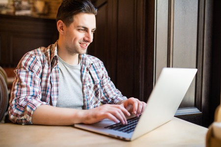 Handsome male entrepreneur typing message to content manager of website of marketing corporation on keyboard of laptop computer arranging meeting to discuss collaboration while sitting in cafe.