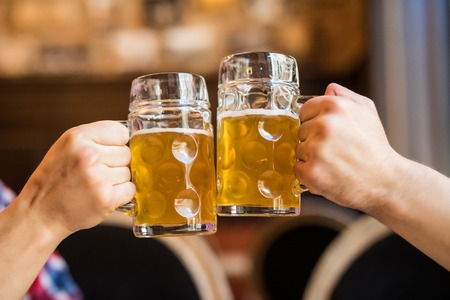 Close-up of people toasts with beer in pub. Beer cheers
