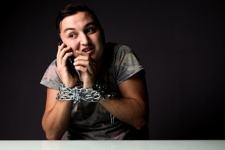 Young Man suffering from phone dependence addiction try to speak in phone with chain on hands