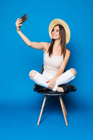 chairs: Pretty girl with long hair in hat chilling in chair on blue background in studio makes selfie-portrait.