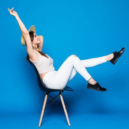 chairs: Pretty girl with long hair in chair on blue background in studio. She wears in summer clothes.