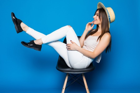 Young smiling woman sitting on chair. Blue background.