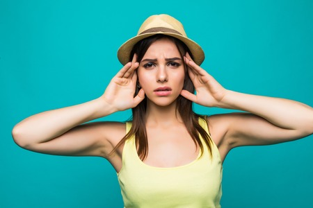 Exasperate female keeps hands on temples, feels strong headache, closes eyes with pain, need healthy sleep, being overworked and tired isolated over green background Stock Photo