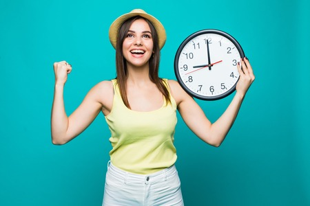 Young woman holding a clock showing nearly 9 with happy victory emotions on green background Stock Photo