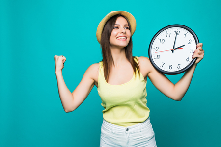 Young woman holding a clock on a green background