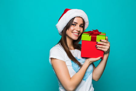 Portrait of a happy smiling girl in dress holding present box and winking isolated over green background Stock Photo