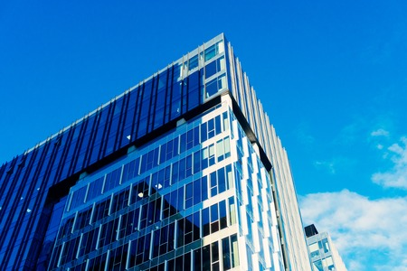 Modern glass skycrapers background with sky and clouds reflection Stock Photo