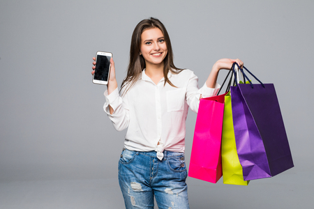 Beautiful woman pointed screen of phone with color shopping bags in hands Фото со стока