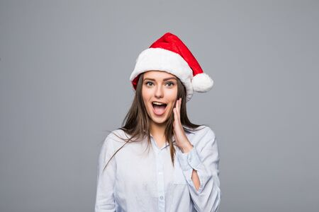 surprised christmas woman wearing a santa hat smiling isolated over a gray background