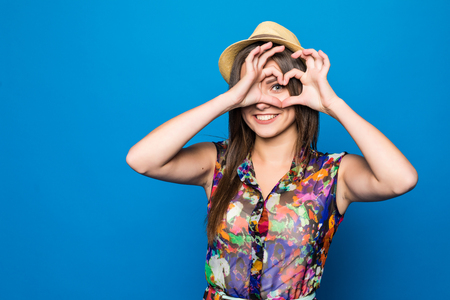 Beautiful young woman in sun hat is showing heart shape hand sign.