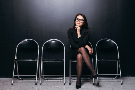 Waiting for interview. Confident young businesswoman sitting on chair against black background Imagens
