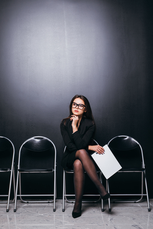 beautiful suit female student holding meeting file sitting on chair and looking at empty area thinking work planning feeling frustrated in black wall room. Archivio Fotografico