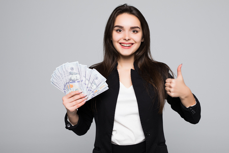 Smiling business woman holding money over gray background
