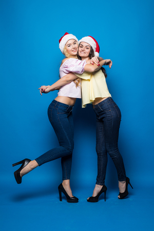 Portrait of cheerful happy women in christmas hats while standing and looking at camera over blue background