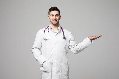 Young and handsome doctor portrait over a white
