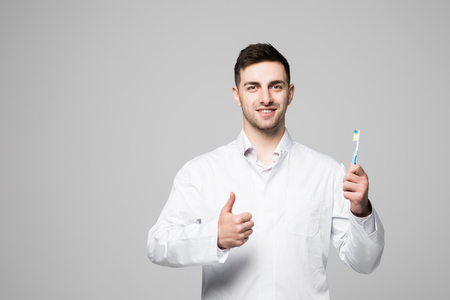 Smiling dentist holding toothbrush and showing thumbs up gesture on white