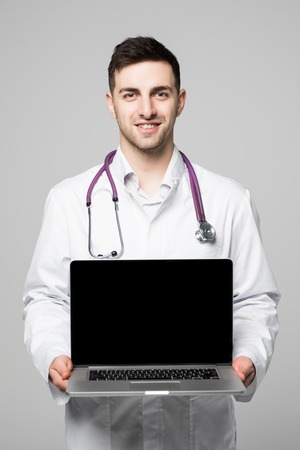 Photo of male doctor, smiling to camera and holding a laptop computer for the blank screen to add your own image of message, isolated on a white background.