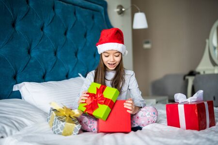 Beautiful little girl in Santas hat opening gift box, looking surprised while sitting on bed at home Stockfoto