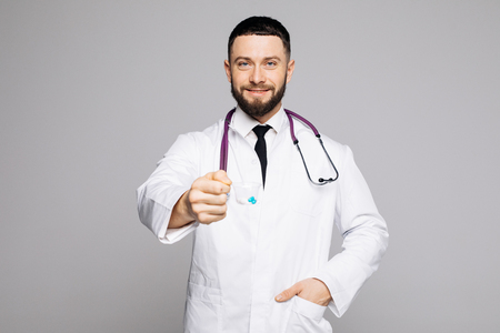 Handsome young doctor with open hands giving pills on white background