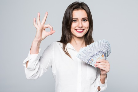 Happy business woman holding us dollar money and gesturing OK sign, over white background Stock Photo