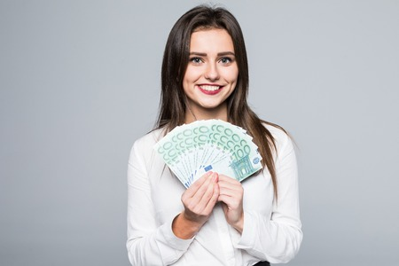 Jonge vrouw die euro geld houdt dat op wit wordt geïsoleerd
