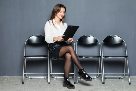 Young woman waiting for job interview with blanck in hands on gray background