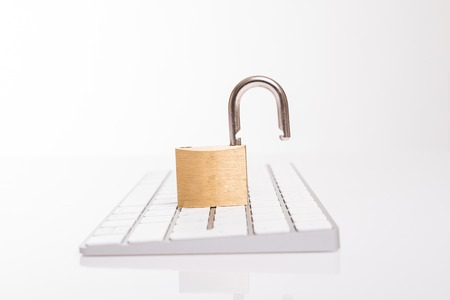 Open steel padlock lying on a white computer keyboard in a low angle view in a concpet of privacy