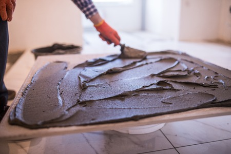 Keramische tegels leggen. Troweling mortel op een betonnen vloer als voorbereiding op het leggen van vloertegel.