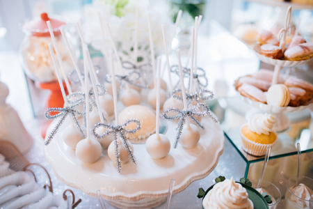 Colorful table with sweets and goodies for the wedding party reception, decorated dessert table. Delicious sweets on candy buffet. Stock Photo