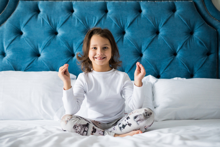 Photo of funny little girl trying to make lotus pose in bed