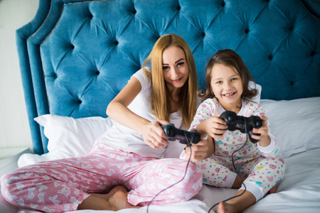 Cheerful mother and daughter playing video games in bed