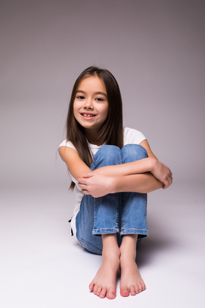closeup image of a pretty little girl sitting on the floor in jeans