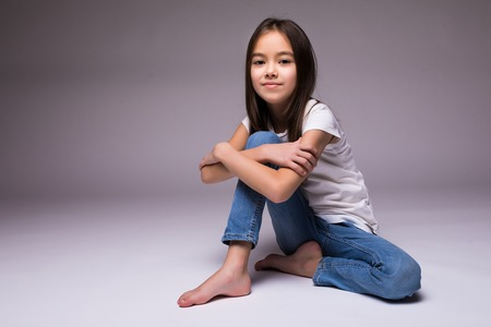 lovely little girl sitting on the floor, isolated on white background Stockfoto