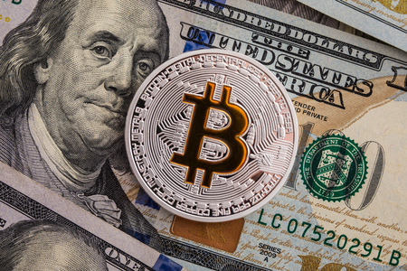 Silver Bitcoin on Us Dollars Banknotes background Stock Photo