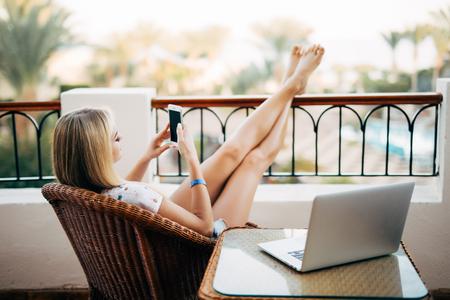 携帯電話を使用して、足を上げて一日の終わりにリラックスする女性 写真素材