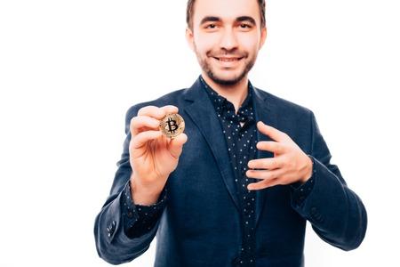 白で隔離されたカメラを指差した手に噛み付いている若いハンサムなビジネスマン