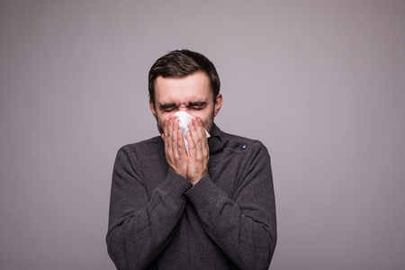 Closeup portrait of sick young man student or worker with allergy or germs cold, blowing his nose with kleenex, looking miserable unwell very sick, isolated on white background.