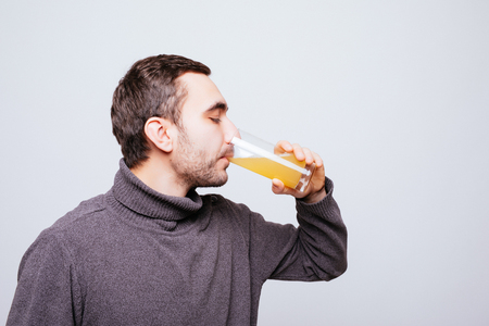 Handsome guy is drinking orange juice, on gray background