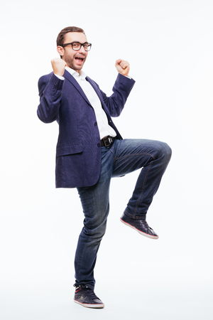 Excited elated happy young business man with beard in classic suit jumping and shouting over white