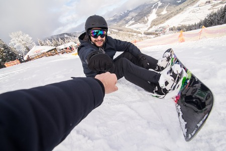 Snowboarder fastens snowboard buckles sitting on the top of snow hill