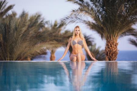 Beautiful woman is relaxing in an infinity pool