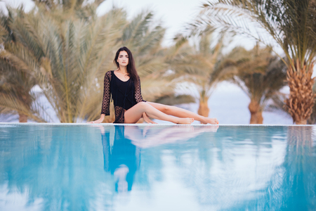Woman in swimsuit reclining at the edge of infinity pool Standard-Bild