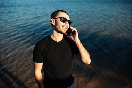 young man talking with mobile phone on the beach Stock Photo