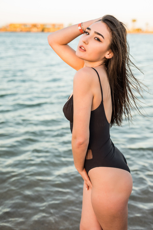 Young woman in swimsuit walking on sea coast. rear view