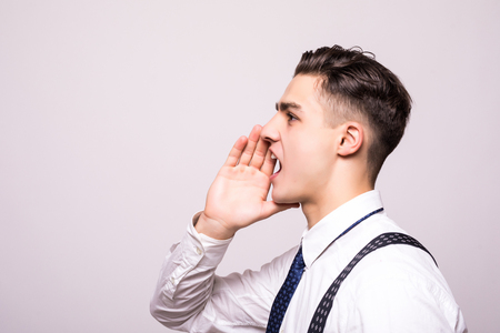 Closeup side view profile portrait, angry upset young man, worker, employee, business man, hand to mouth, open mouth yelling, isolated white background. Stock Photo