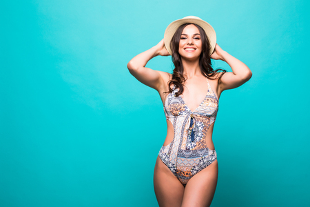 Attractive woman with pink swimwear and straw hat isolated on green background
