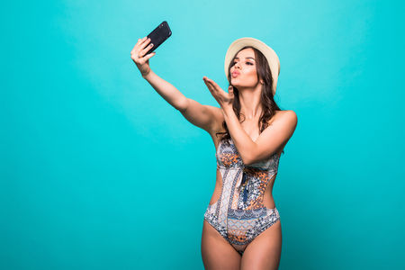 Lovely girl dressed in swimsuit and summer hat taking a selfie isolated over green background