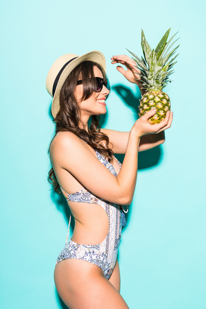 Portrait of young woman in swimsuit with pineapple on blue background. Summer season