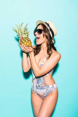 young beautiful woman in bikini and straw hat, sunglasses with pineapple isolated on blue
